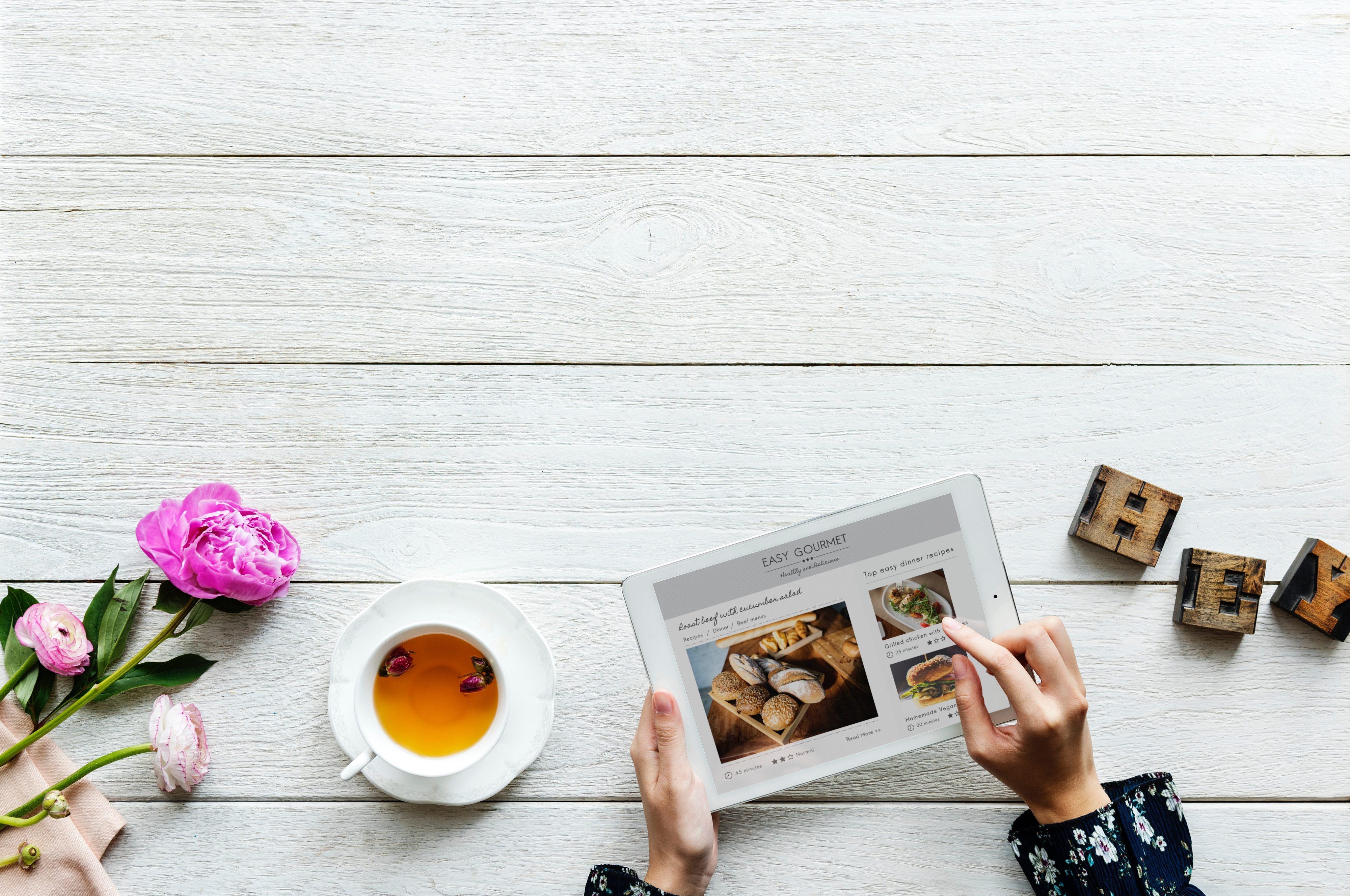 leggere l'ipad alla scrivania, con caffè e altri props