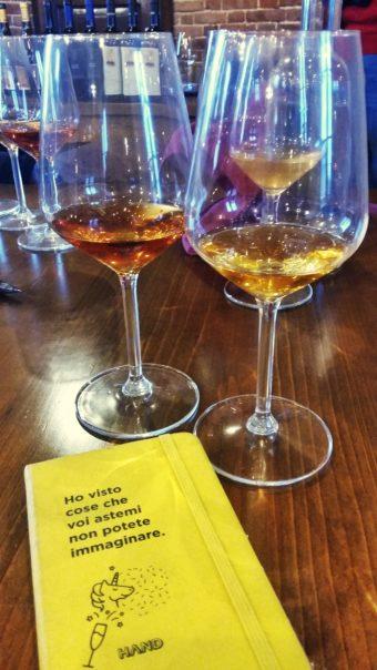 calici di orange wine e bloc-notes